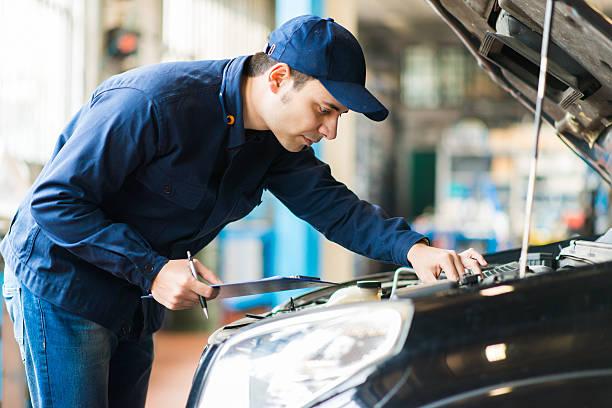 mechaniker bei der arbeit in der garage - checking stock-fotos und bilder