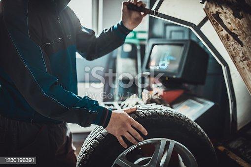 istock Mechanic balancing a tire in auto repair shop 1230196391
