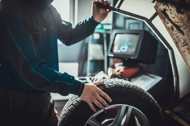 Mechanic balancing a tire in auto repair shop stock photo