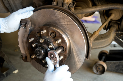 mechanic using a socket wrench to remove the bolts holding on the disc brake rotor and wheel hub