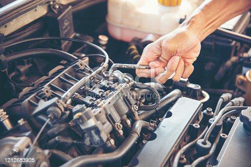 1137474295 istock photo Mechanic Car Service in automobile garage auto car and vehicles service mechanical engineering. Automobile mechanic hands car repairs automotive technician workshop center. Services car engine machine 1212683925