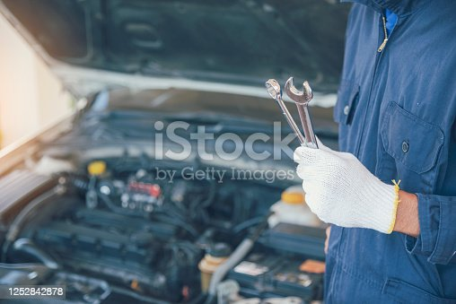 962888586 istock photo Mechanic Car Service in automobile garage auto car and vehicles service mechanical engineering. Automobile mechanic hands car repairs automotive technician workshop center. Services car engine machine 1252842878