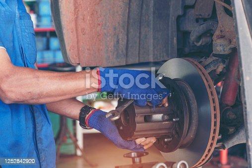 962888586 istock photo Mechanic Car Service in automobile garage auto car and vehicles service mechanical engineering. Automobile mechanic hands car repairs automotive technician workshop center. Services car engine machine 1252842920