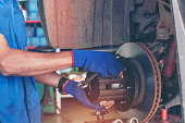 istock Mechanic Car Service in automobile garage auto car and vehicles service mechanical engineering. Automobile mechanic hands car repairs automotive technician workshop center. Services car engine machine 1252842920