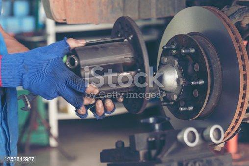 962888586 istock photo Mechanic Car Service in automobile garage auto car and vehicles service mechanical engineering. Automobile mechanic hands car repairs automotive technician workshop center. Services car engine machine 1252842927
