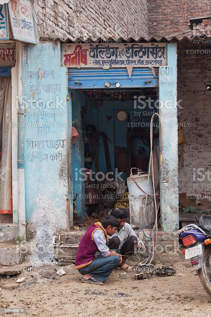 Mechanic carrying out repairs at an Indian roadside auto shop stock photo