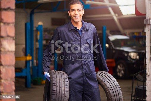 599909112 istock photo Mechanic carrying two tyres 599975940