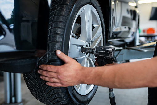 Germany: A mechanic changes a tire in a car repair shop.