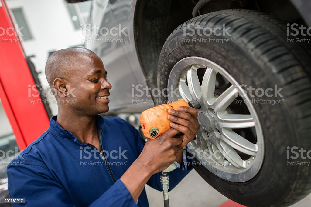 Mechanic changing a wheel stock photo