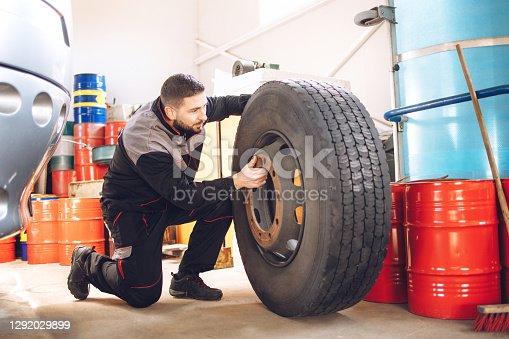 istock Mechanic changing bus wheel in  repair shop. 1292029899