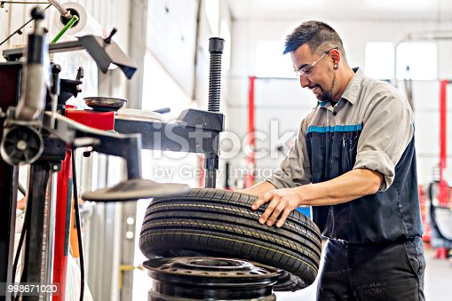 A Mechanic changing car tire at work