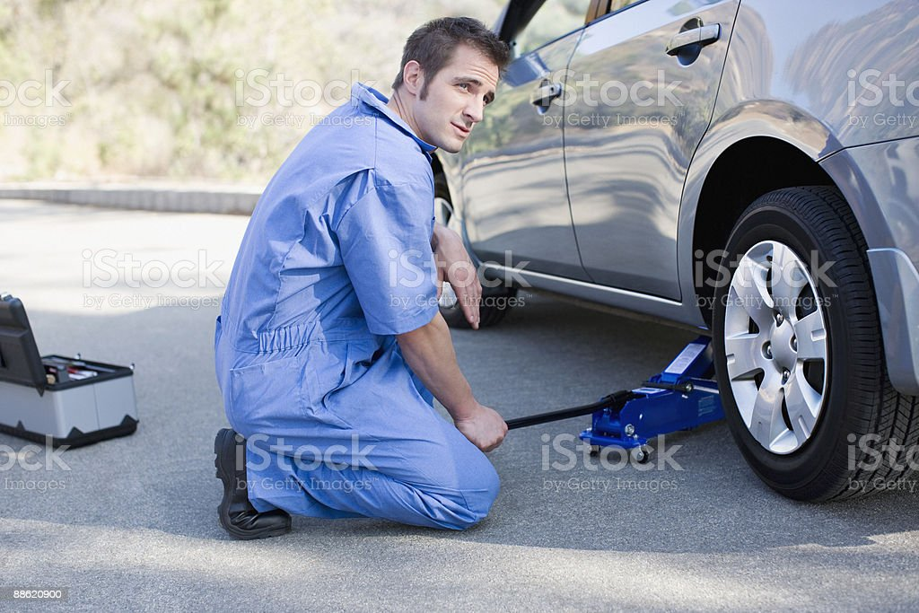 Mechanic changing cars flat tire stock photo