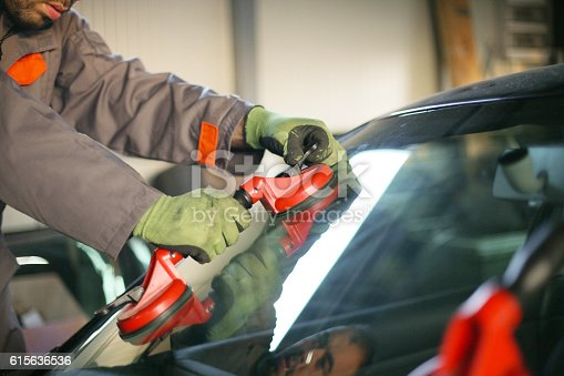 istock Mechanic changing glass on car. 615636536
