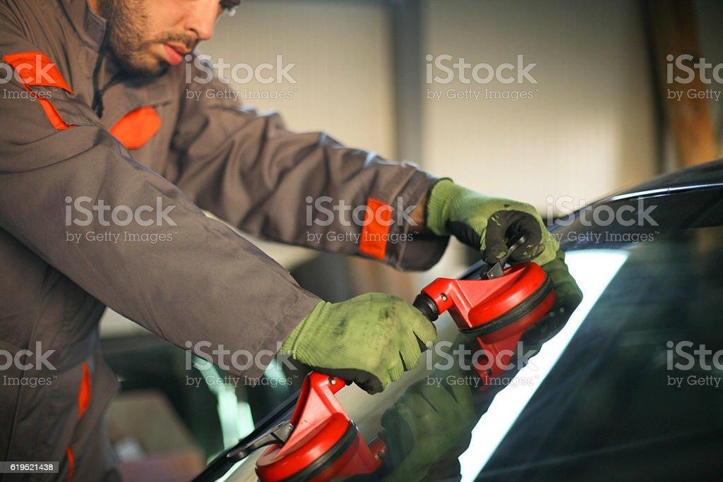 Mechanic changing glass on car. – zdjęcie