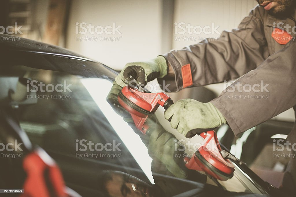 Mechanic changing glass on car. – zdjęcie
