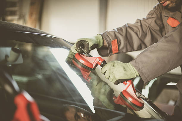 mechanic changing glass on car. - auto body repair stock photos and pictures