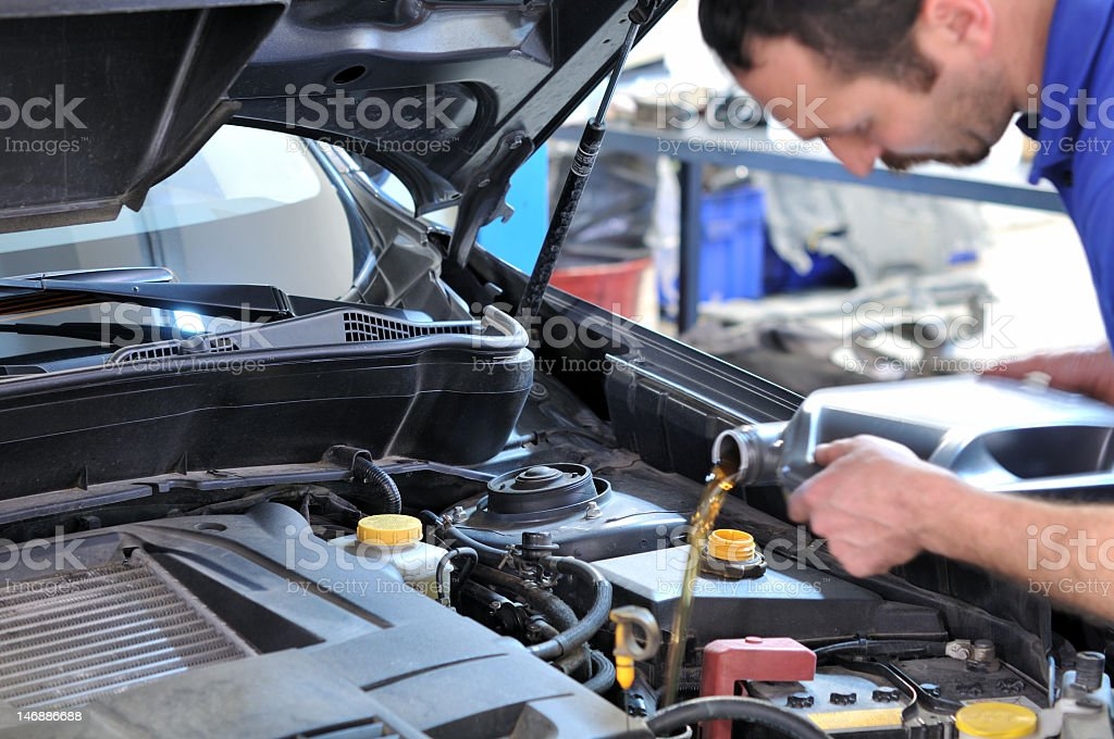 Mechanic changing oil in automobile  stock photo