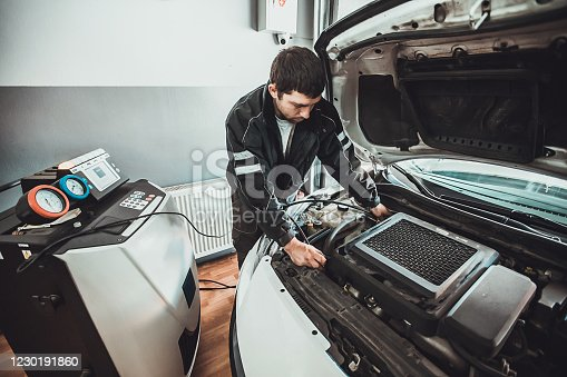 One young auto mechanic doing service of car's air conditioning system in repair shop.