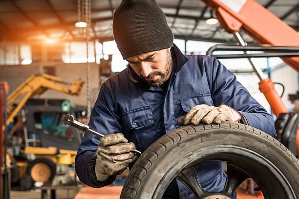 Mechanic, check depth of tire – Foto