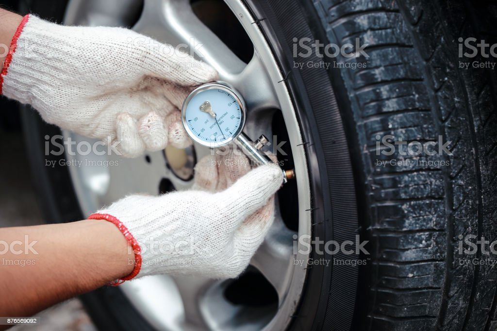 mechanic check the tire air pressure stock photo