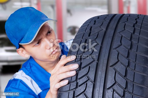 1047558948 istock photo Mechanic checking a textured tire 468393142