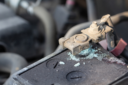 istock Mechanic checking car Battery terminalin a garage. Old battery corrosion deteriorate leaking with blue acid powder. Battery terminals corrode dirty damaged problem. 1144170303