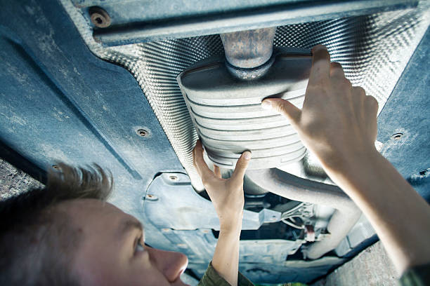 Mechanic checking exhaust pipe Male mechanic replacing exhaust pipe under car socket wrench stock pictures, royalty-free photos & images