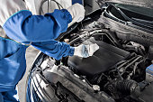 istock Mechanic checking oil level in a car workshop 701038882