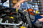 Unrecognizable Person, an Auto mechanic working in the garage. Repair service. Close up of a car mechanic checking the oil level in a mechanical workshop. Male mechanic in uniform is working in auto service. Car repair and maintenance. Side view of a mechanic checking motor oil in a car with open hood.
