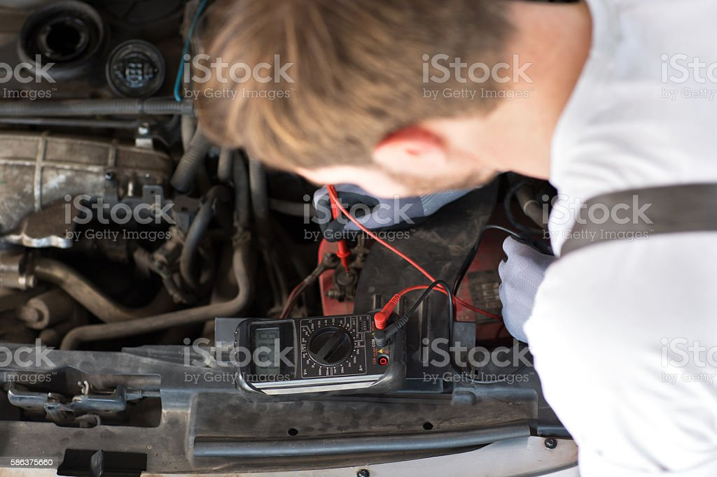 mechanic checks electronics accumulator stock photo