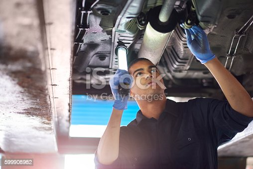 A young mechanic is working under a car in a garage repair shop. He is wearing blue overalls.  He is looking up with an inspection lamp to check the possible damage that has been sustained to the exhaust.