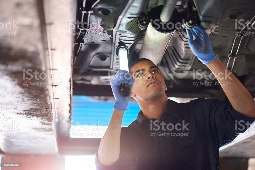 Mechanic checks exhaust stock photo