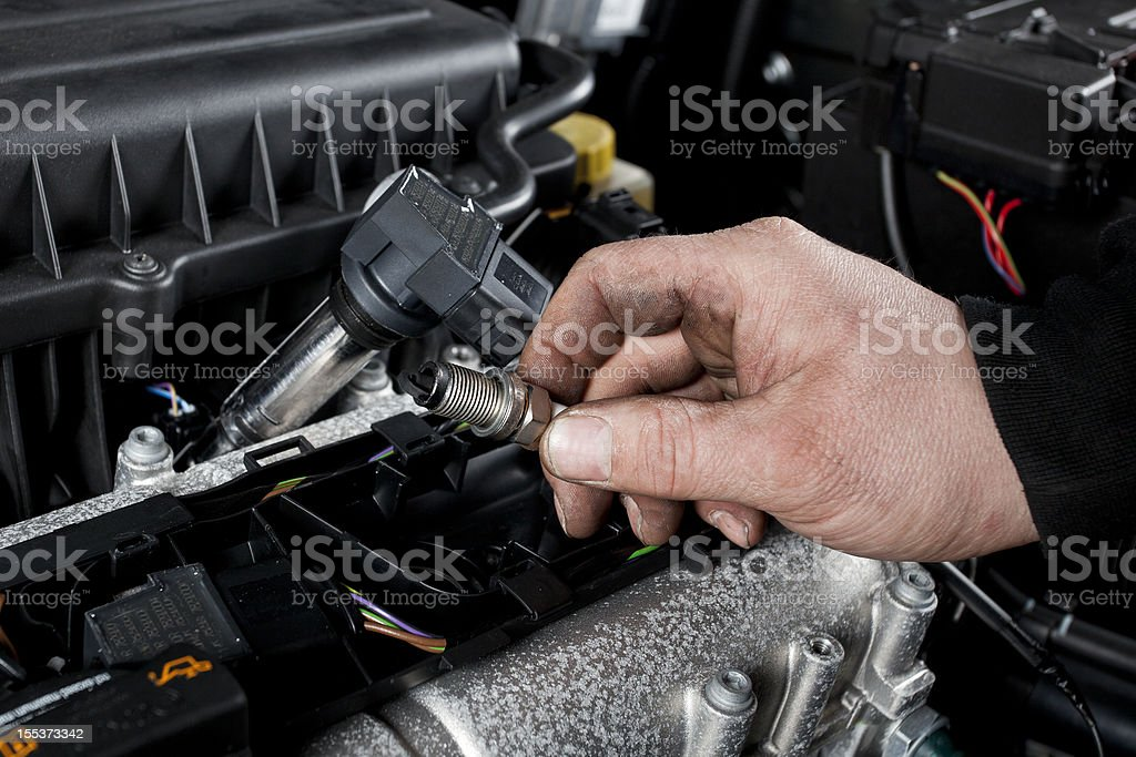 Mechanic checks the ignition plugs of a modern car royalty-free stock photo