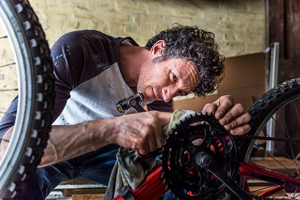 Mechanic cleaning gear of bicycle with cloth stock photo