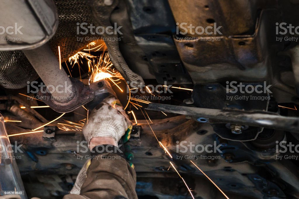 mechanic cleans silencer pipe by angle grinder stock photo