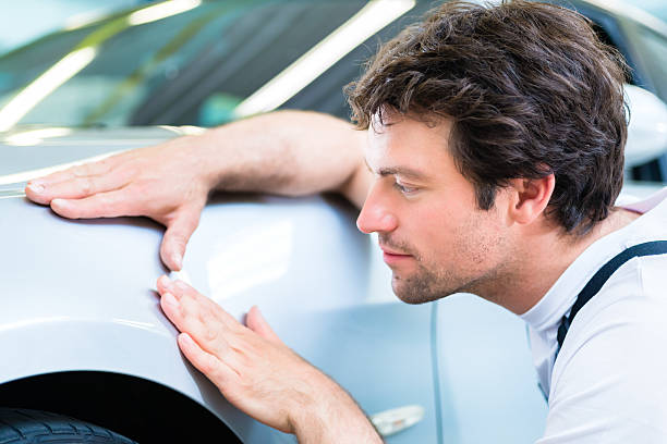 Mechanic controlling lacquer in car workshop Male mechanic examine car finish on dents or scratches in workshop lacquered stock pictures, royalty-free photos & images