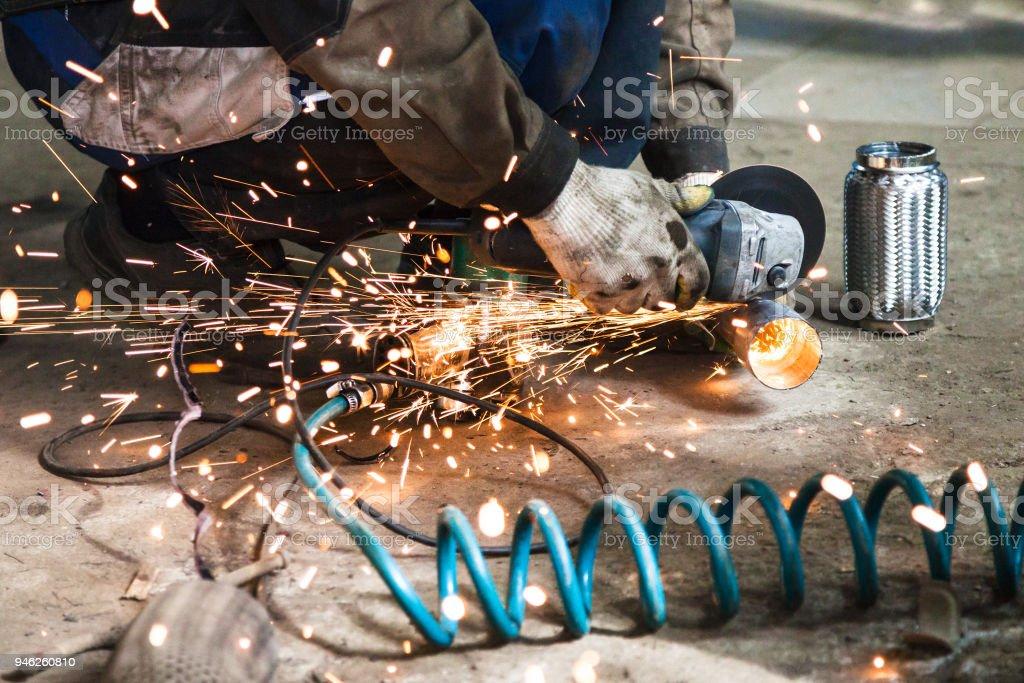 mechanic cuts new pipe for corrugation muffler stock photo
