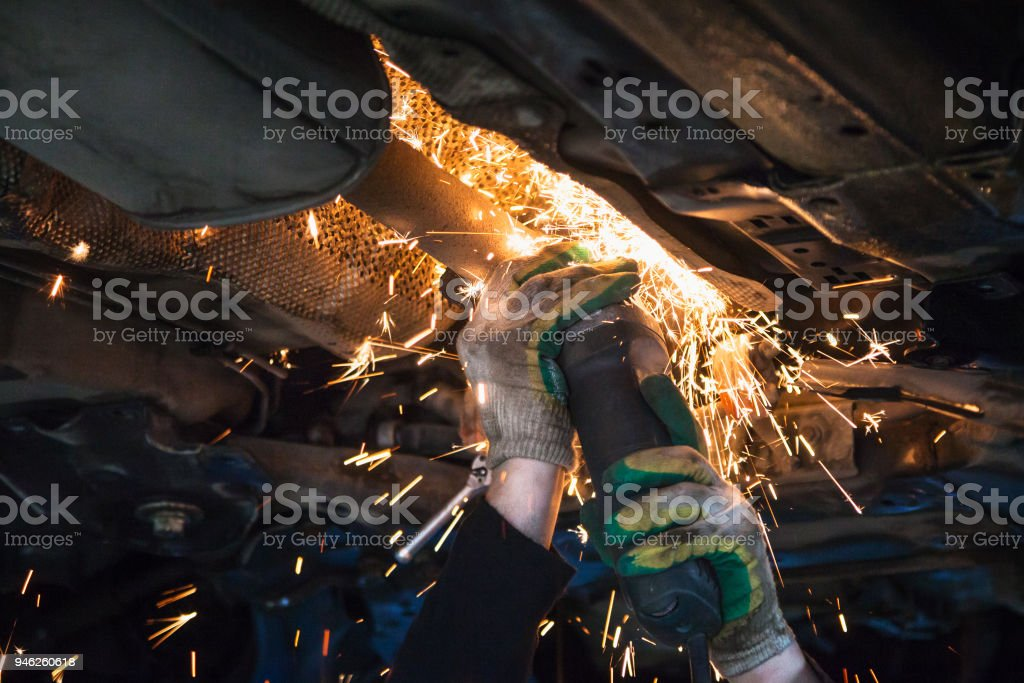 mechanic cuts old muffler on car by angle grinder stock photo