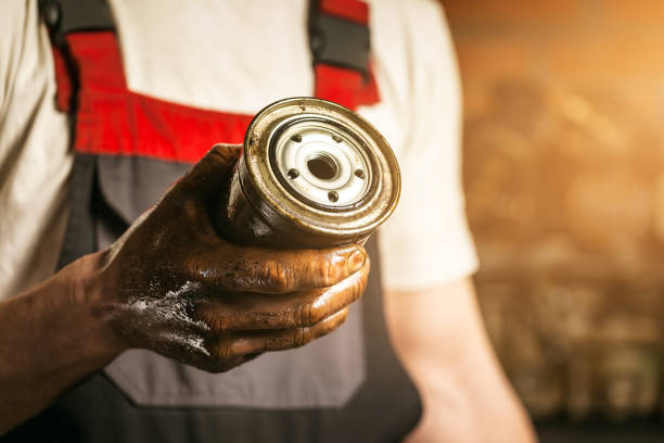 Mechanic. Dirty hands holding oil filter. stock photo