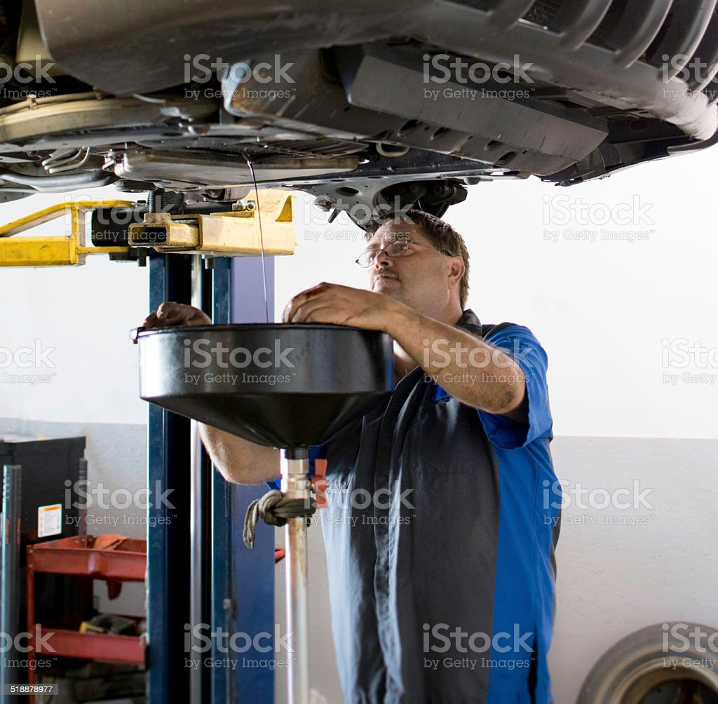 Mechanic draining automotive fluids stock photo