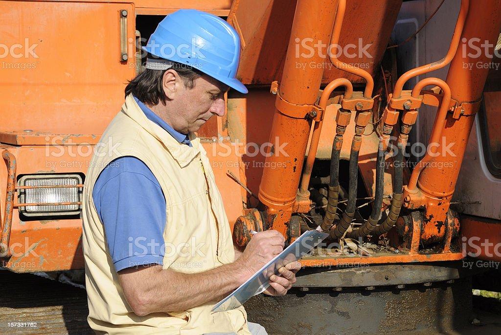 Mechanic Examining Bulldozer royalty-free stock photo