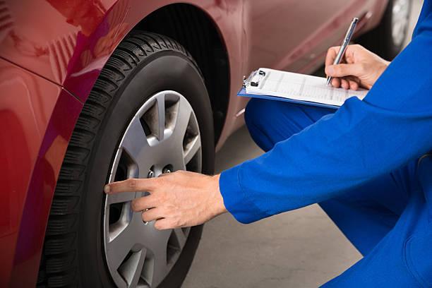 Mechanic Examining Car Wheel stock photo