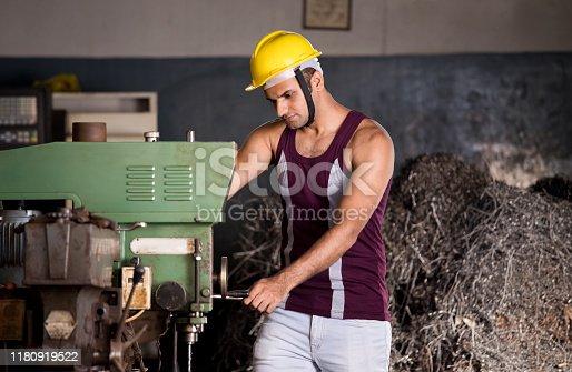 1047558948istockphoto Mechanic examining machine at factory 1180919522
