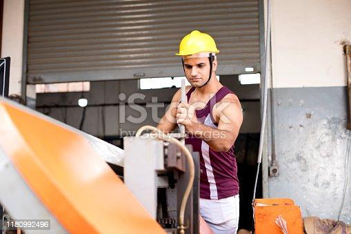 1047558948istockphoto Mechanic examining machine at factory 1180992496