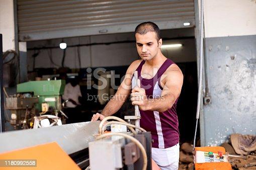 1047558948istockphoto Mechanic examining machine at factory 1180992558