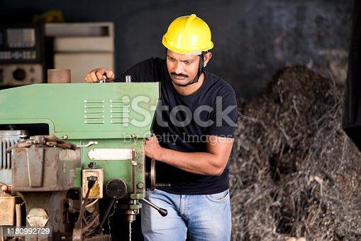 1047558948istockphoto Mechanic examining machine at factory 1180992729