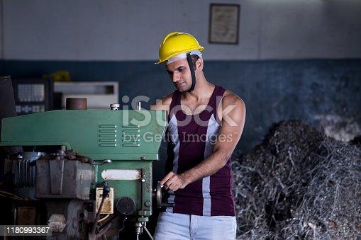 1047558948istockphoto Mechanic examining machine at factory 1180993367