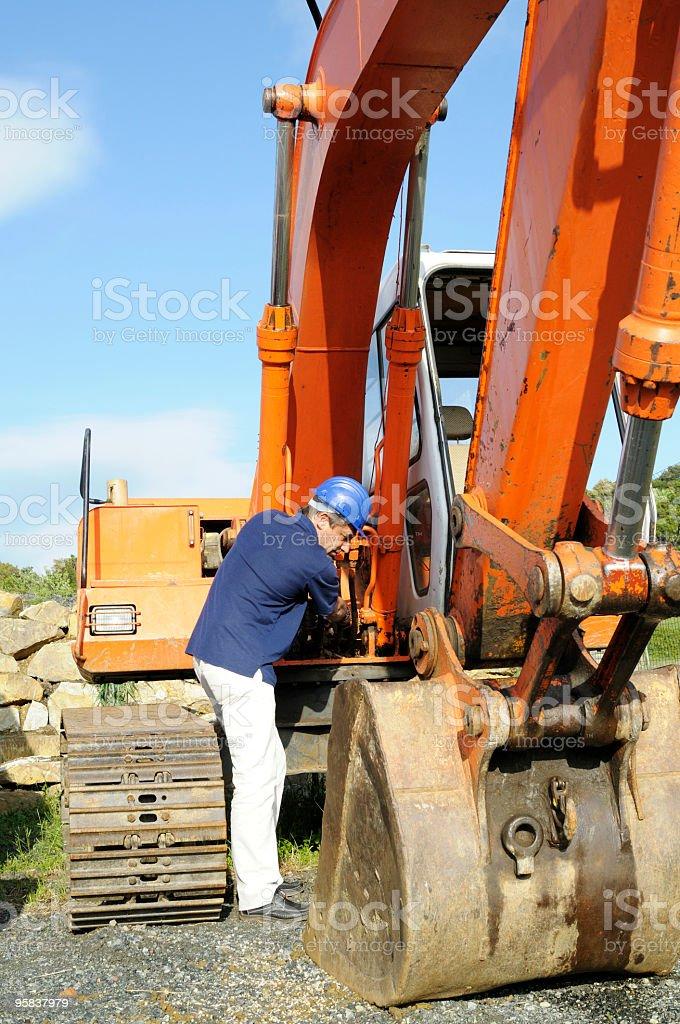 Mechanic examining the excavator royalty-free stock photo
