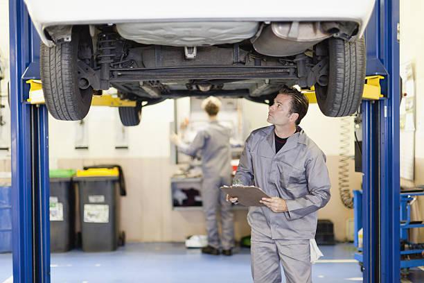 mechaniker prüfung der unterseite des autos - autowerkstatt stock-fotos und bilder