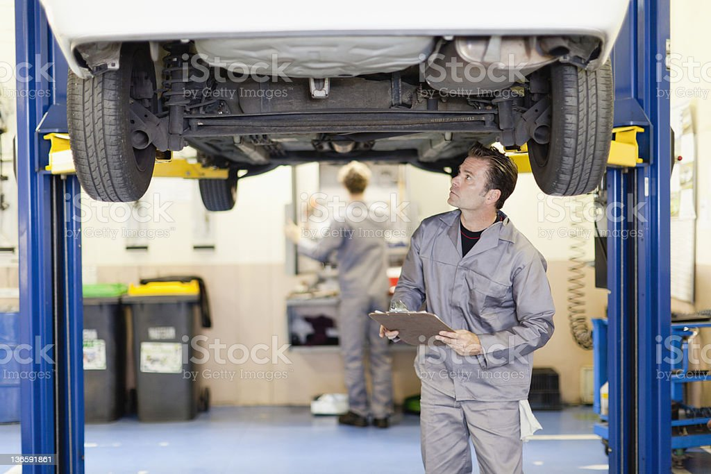 Mechanic examining underside of car stock photo